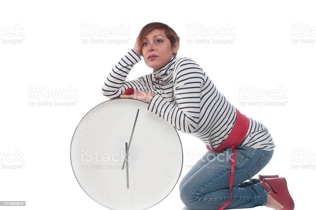 Caucasian Woman Looking Worried While Leaning On A Clock stock photo
