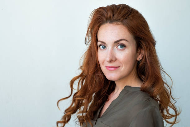 Caucasian woman model with ginger hair posing indoors stock photo