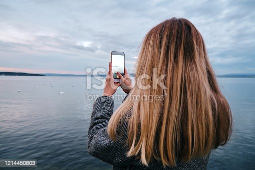 Caucasian woman photographs sunset on smartphone. Girl holding a mobile phone. Camera app. Beautiful autumn evening near the lake. Walk in nature, relaxed lifestyle. Photos for social networks