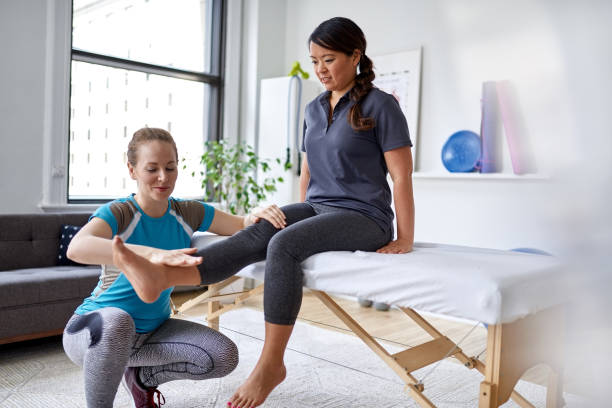 Caucasian woman physiotherapist strectching the leg and knee of a mid-adult chinese female patient sitting on a massage table stock photo