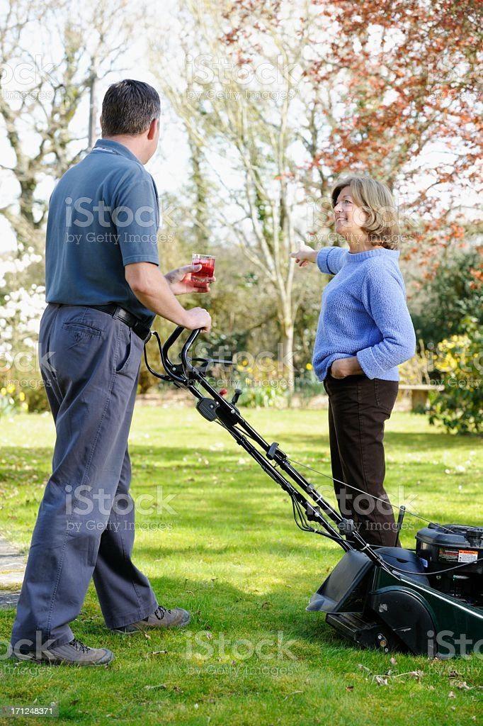 Caucasian Woman Pointing Out  Area That Needs AttentionTo Gardener royalty-free stock photo