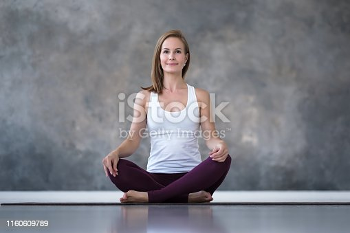 Caucasian woman practicing yoga, doing sukhasana or easy seat pose, working out. Indoor full length studio shot
