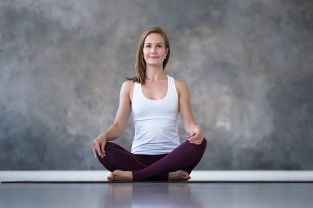 caucasian woman practicing yoga, doing sukhasana or easy seat pose - poprawna postawa zdjęcia i obrazy z banku zdjęć