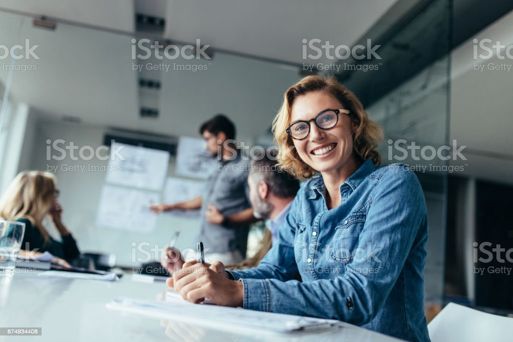 Caucasian woman sitting in board room during presentation stock photo