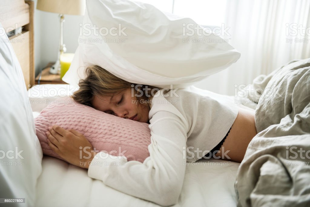 A Caucasian woman sleeping on her bed stock photo