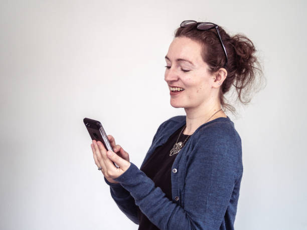 Caucasian woman smiling at her mobile phone stock photo