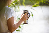 istock Caucasian woman standing by river with coffee-drink 1183936209