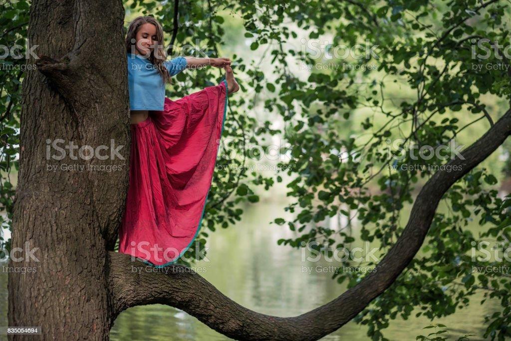 Caucasian woman standing in yoga balance Utthita Hasta Padangusthasana pose. She hold trank of tree stock photo