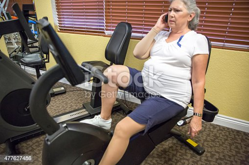 912333752 istock photo Caucasian woman uses cell phone on stationary bike at therapist 477627486