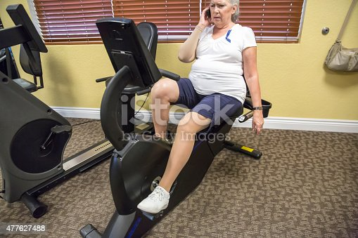912333752 istock photo Caucasian woman uses cell phone on stationary bike at therapist 477627488