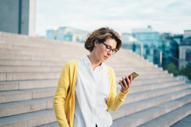 kaukasische frau mit smartphone im freien - brille bestellen stock-fotos und bilder