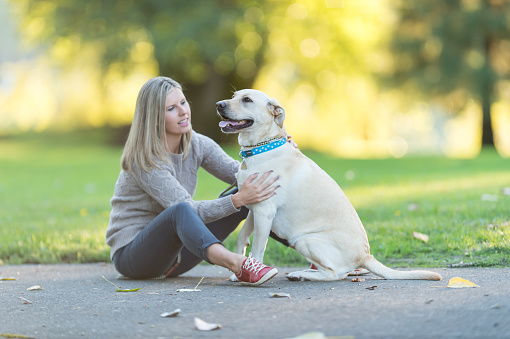Caucasian woman walks her dog on beautiful summer evening in park
