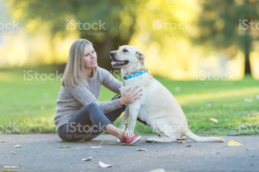 Caucasian woman walks her dog on beautiful summer evening in park stock photo