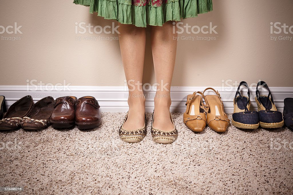 Caucasian woman wearing skirt and flats standing against a wall royalty-free stock photo