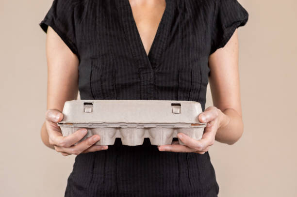 Caucasian woman with black shirt holding a cardboard egg box full of chicken eggs stock photo