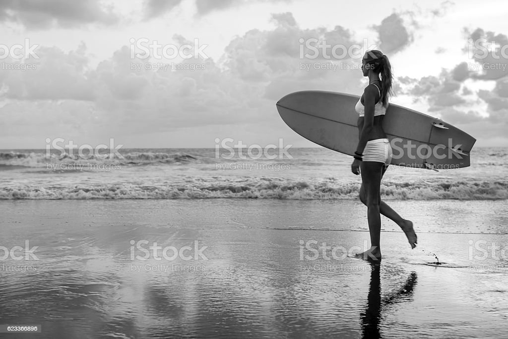Caucasian woman with surfboard on the beach going to surf stock photo