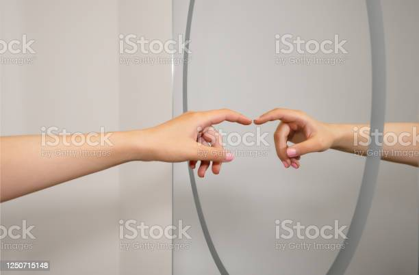 Photo of A caucasian woman's hand reflected in a clean bathroom mirror as she reaches out and almost touches. A representation a social distancing and hygiene concept.
