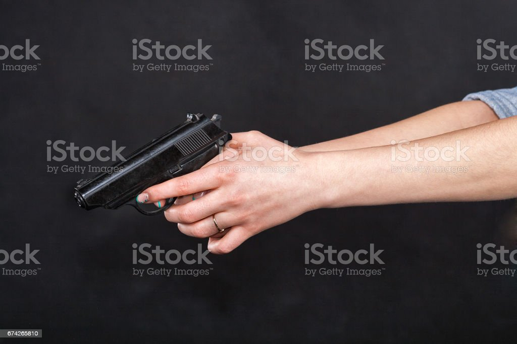Caucasian women arms holding a gun against black background Caucasian women outstretched arms holding a black gun, fingers on the trigger. Against black background. Adult Stock Photo