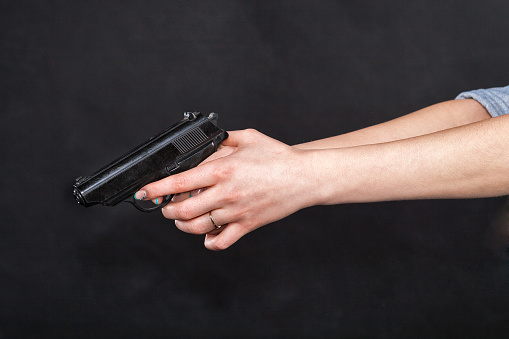 Caucasian Women Arms Holding A Gun Against Black Background Stock Photo - Download Image Now