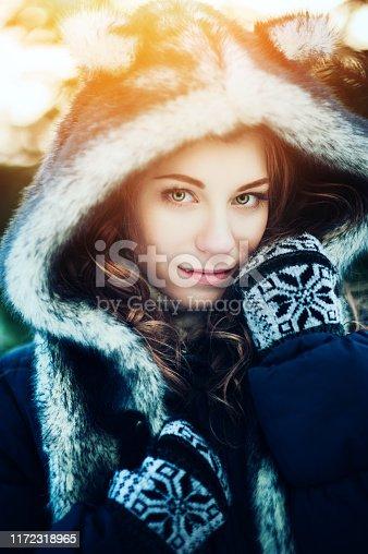 Caucasian young beautiful happy girl smiling winters outdoor shots, Model wearing stylish winter fur wolf hat