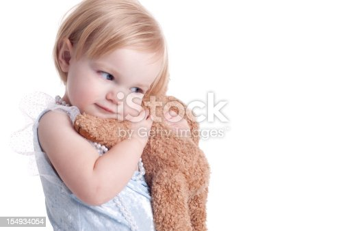Cute little girl wearing pearls and a blue tutu, hugging a stuffed animal.