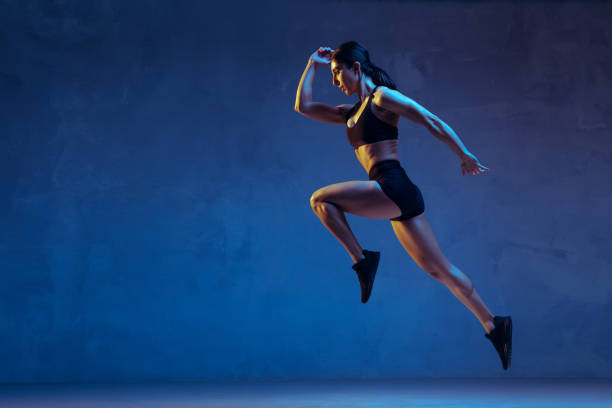 Caucasian young female athlete practicing on blue studio background in neon light stock photo