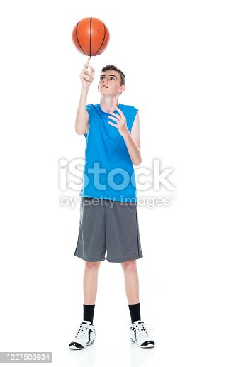 One person of aged 12-13 years old caucasian young male basketball player spinning in front of white background and holding basketball - ball and using sports ball