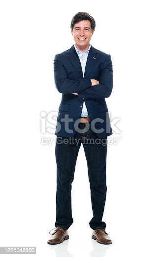 Full length of aged 20-29 years old with brown hair caucasian young male business person standing in front of white background wearing jeans who is successful with arms crossed