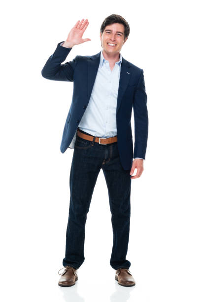 Caucasian young male business person standing in front of white background wearing jeans stock photo