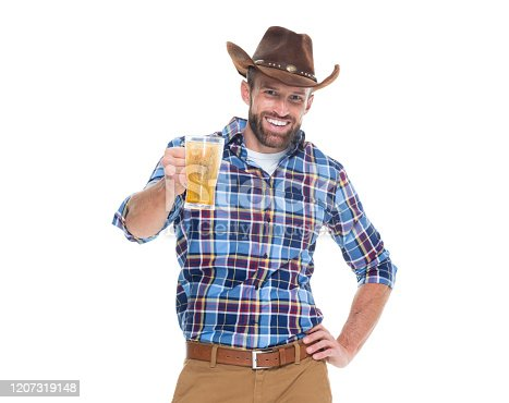 Front view of caucasian young male cowboy celebratory toast in front of white background wearing hat who is drinking and showing hand raised with hand on hip and holding pint glass