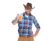 istock Caucasian young male cowboy celebratory toast in front of white background wearing hat and holding pint glass 1207319148