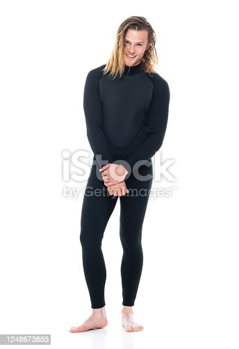Front view of aged 20-29 years old with long hair caucasian young male in front of white background wearing swimwear who is showing cool attitude who is barefoot