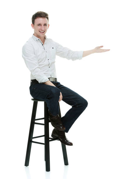 Caucasian young male presenter sitting in front of white background wearing button down shirt stock photo