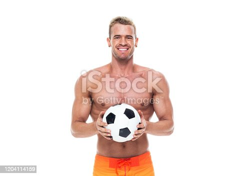 istock Caucasian young male soccer player standing wearing swimwear and holding soccer ball 1204114159