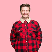 Waist up of aged 20-29 years old with short hair caucasian young male standing in front of colored background wearing warm clothing who is showing cool attitude