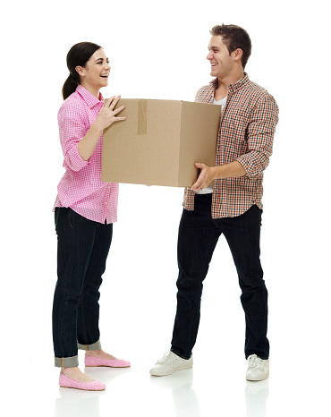 istock Caucasian young male standing in front of white background wearing jeans and holding cardboard box 1210912161