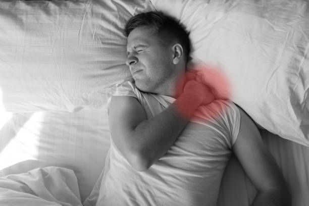 caucasian young man having terrible pain in neck in bed in the morning - ernia foto e immagini stock