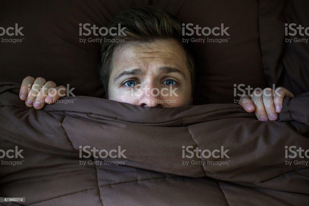 Hombre joven caucásico escondiendo en la cama debajo de la manta en casa. - foto de stock
