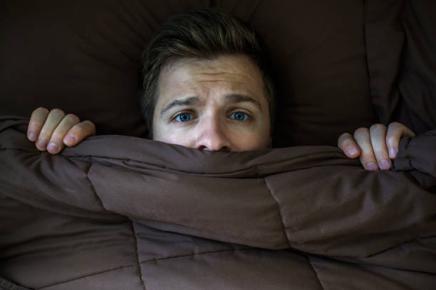 caucasian young man hiding in bed under the blanket at home. - fear stock photos and pictures