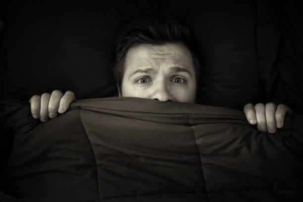 Caucasian young man hiding in bed under the blanket at home. Caucasian young man hiding in bed under the blanket at home. He is stressed and tries run away from problems. Black and white photo paralysis stock pictures, royalty-free photos & images