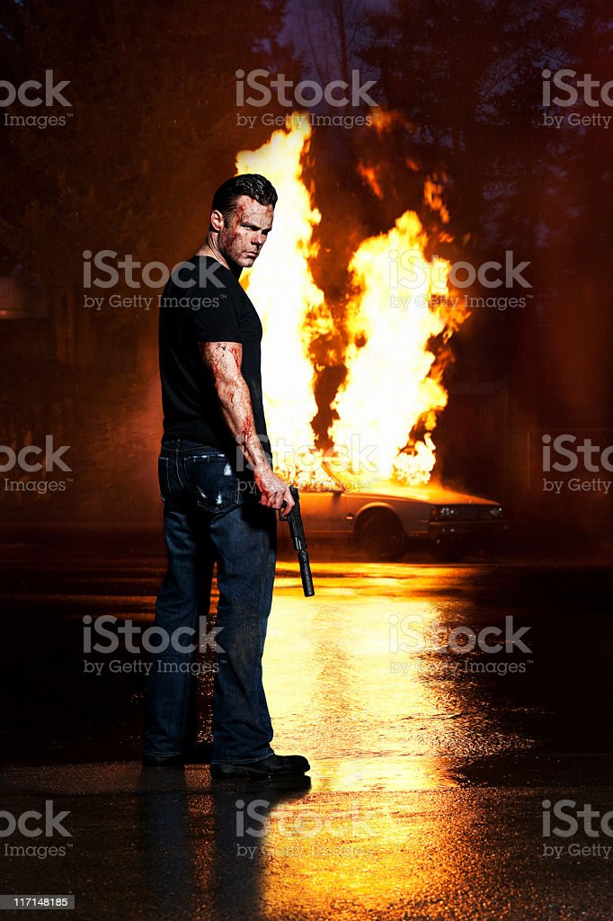 Angry, Bloody Man Holding Gun, Posing with Car on Fire stock photo