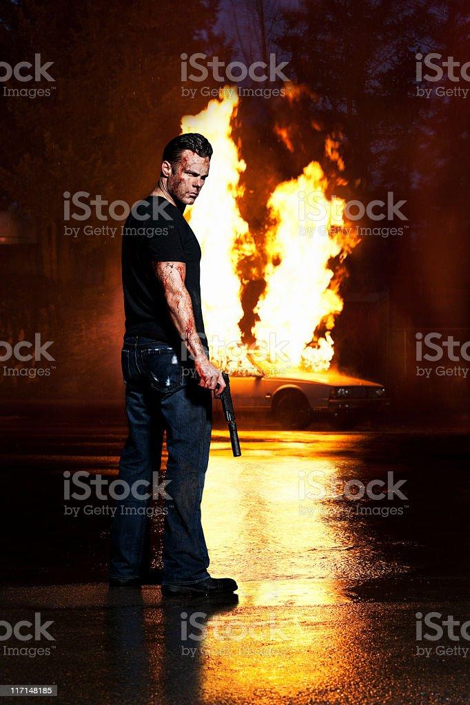 Angry, Bloody homem segurando arma, posando com automóvel em fogo - foto de acervo