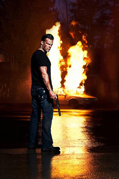 Enojado, Man Holding Bloody pistola, posando con coche de fuego - foto de stock