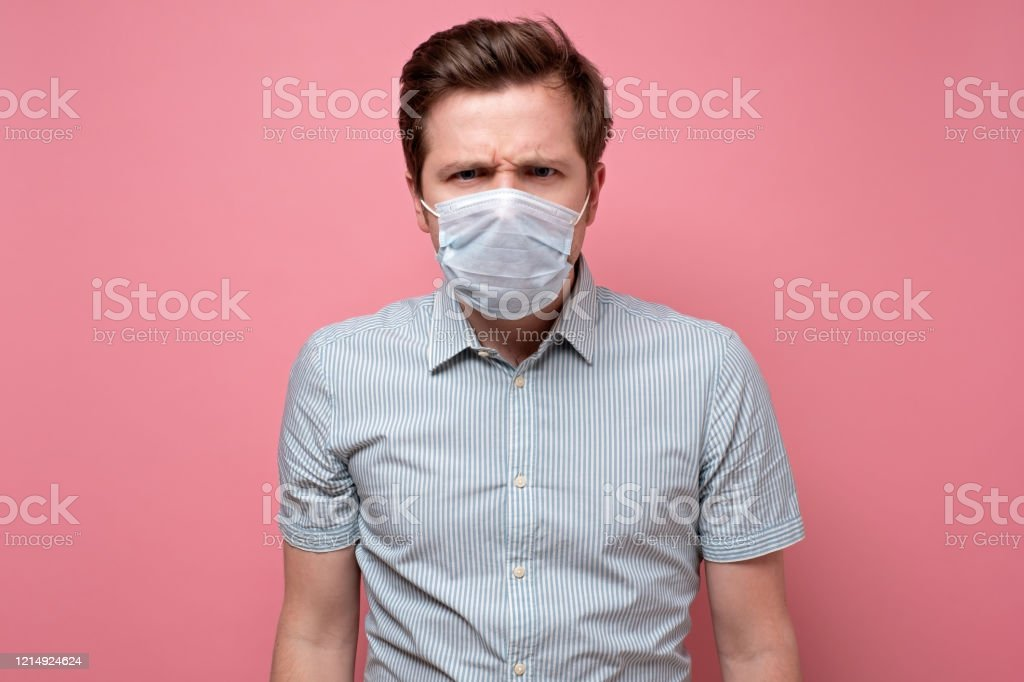 Caucasian young man wearing medical mask trying to protect from flu Caucasian serious young man wearing medical mask trying to protect from flu or coronavirus. Studio shot on pink wall. Adult Stock Photo