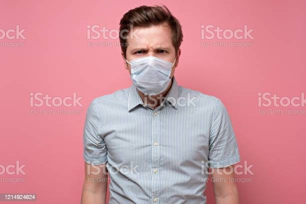 Caucasian Young Man Wearing Medical Mask Trying To Protect From Flu Stock Photo - Download Image Now