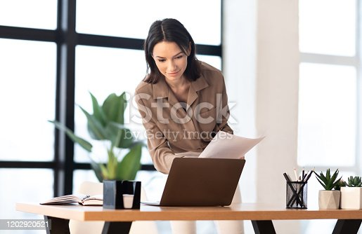 1031394390 istock photo Caucasian young woman holding documents at office 1202920521