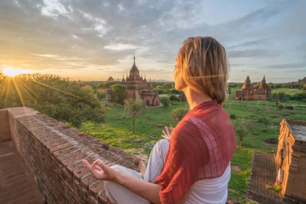 kaukasische junge frau an der archäologischen zone von bagan zu meditieren, bei sonnenaufgang, myanmar - klosterurlaub stock-fotos und bilder