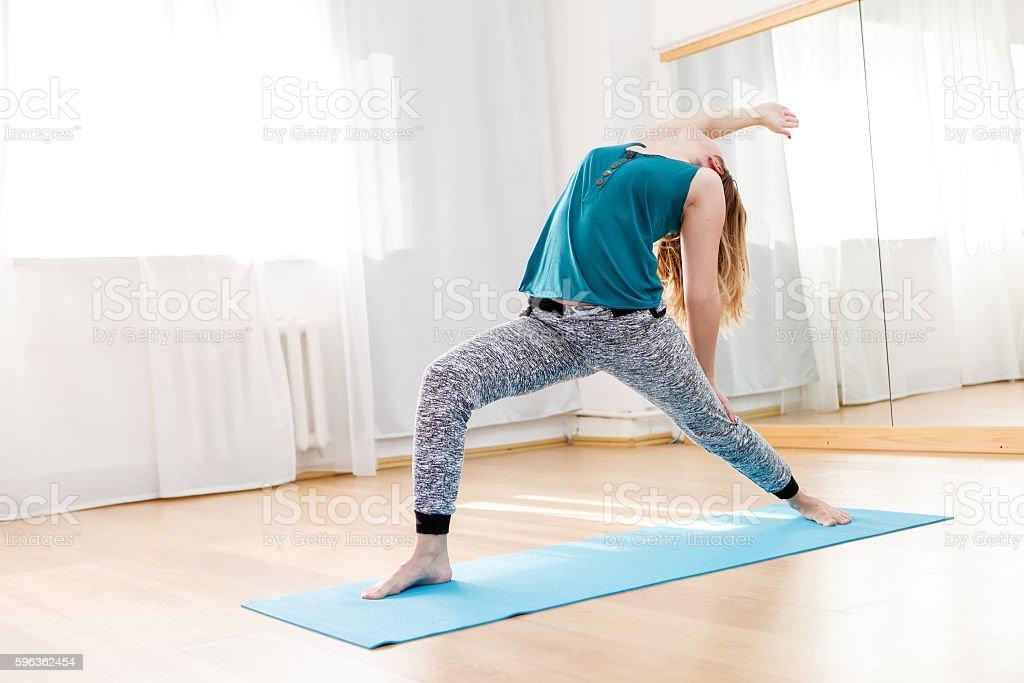 Caucasian young woman practicing virabhadrasana, high lunge asana royalty-free stock photo