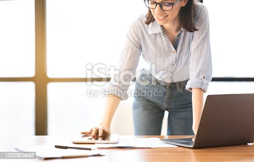 1031394390 istock photo Caucasian young woman using tablet that lying on table 1202920688