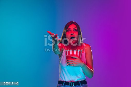 Astonished, eating popcorn. Caucasian young woman's portrait on gradient background in neon light. Beautiful female model. Concept of human emotions, facial expression, sales, ad, movie, cinema.